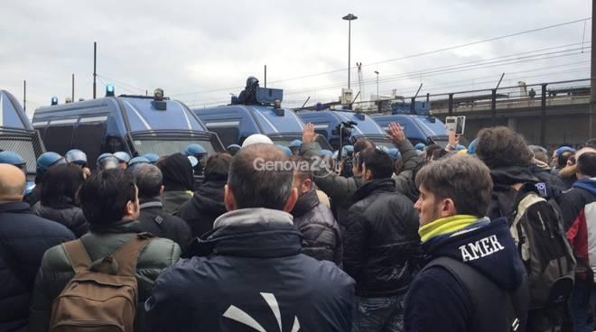 Lavoratori dell'Ilva con le mani alzate davanti alla polizia