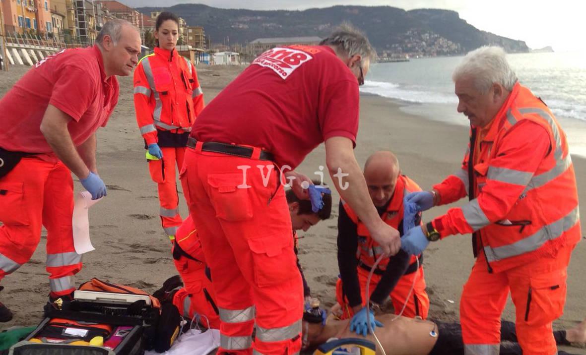 uomo agonizzante in spiaggia