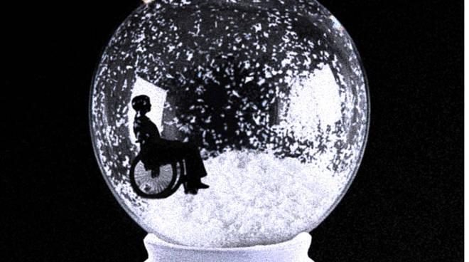 Sfera cristallo con neve e donna in sedia a rotelle